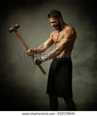 fighter with hammer on hands, dark and foggy background - stock photo