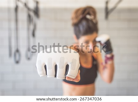 fighter woman fist close up. straight focus on the glove with the rest of the image on blur. concept about sport and people - stock photo