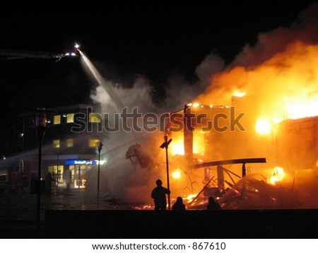 Fighting a flaming building (some noise) - stock photo