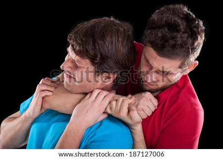 Fighting men friends on isolated black background - stock photo
