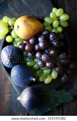 figs and grapes in a wooden bowl, rustic still life - stock photo