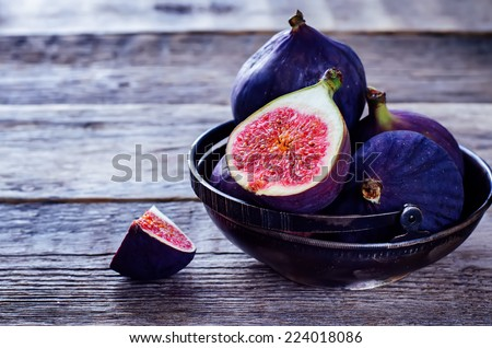 figs on a dark wood background. tinting. selective focus on the front figs slice in the bowl - stock photo