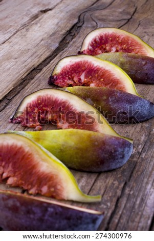 Figs on wood sliced and arranged artistically at an angle portrait - stock photo