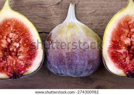 Figs whole and halved shot on wood top view - stock photo
