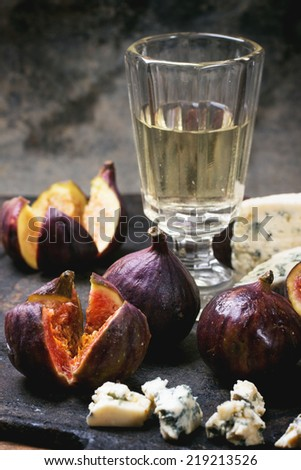 Figs with blue cheese, white wine and crackers on black cutting board. See series.