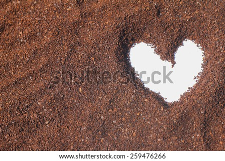 figure drawings in the shape of a heart on the cocoa powder scattered on a white background - stock photo