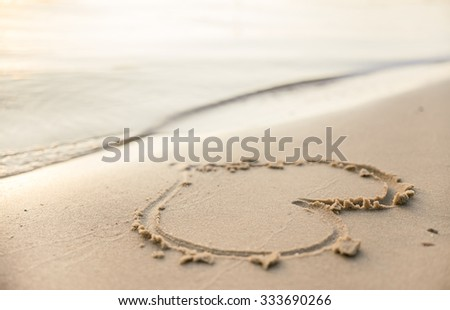 Figure heart in the sand on the beach - stock photo