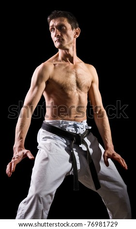 figure in the karate fighting stance on a black background.hand-to-hand fighting.sportsman - stock photo