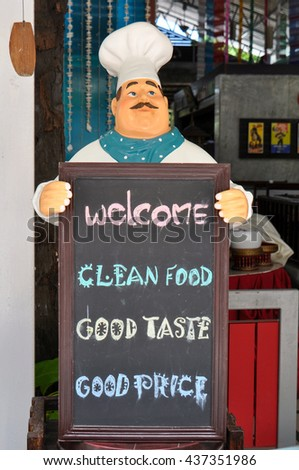 Figure of a cook at a cafe with a sign inviting on Kata beach Phuket - stock photo