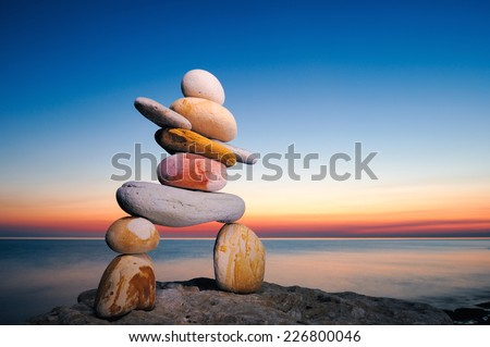 Figure of inukshuk on the seacoast against the sunset - stock photo