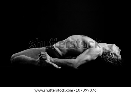 Figure of the young man in sportswear on a dark background - stock photo