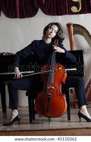 Figure of the young violoncellist in a dark suit - stock photo