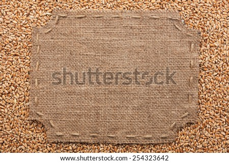 Figured frame with burlap and stitches with  place for your text lying  on wheat  grains as a background