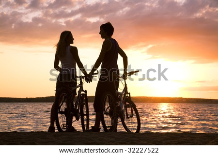Figures of couple standing on seashore with their bicycles and looking at each other at sunset
