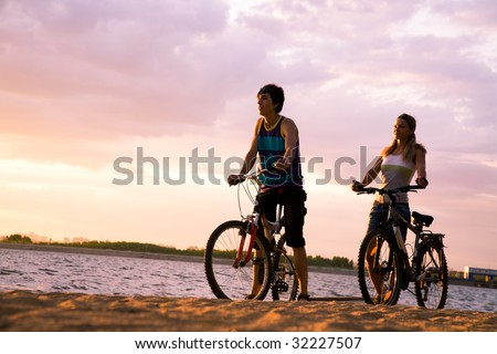 Figures of happy couple standing on seashore with their bicycles and enjoying sunset