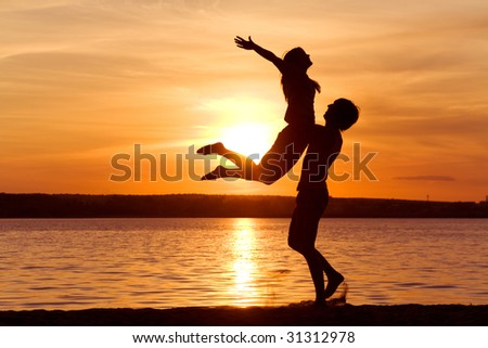 Figures of happy guy holding his girlfriend while the latter raising her arms at sunset - stock photo