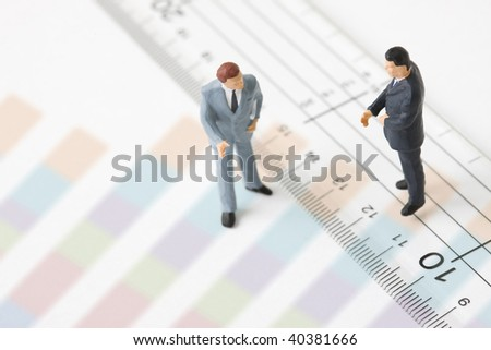 Figures of the businessmen who stands as the side of a ruler. - stock photo