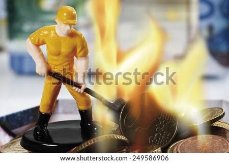 Figurine burning money, close up - stock photo