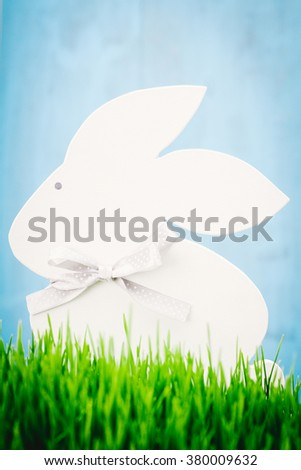 Figurine hare standing in the grass on a blue background. - stock photo