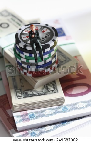 Figurine sitting on jetons with banknotes, close up - stock photo