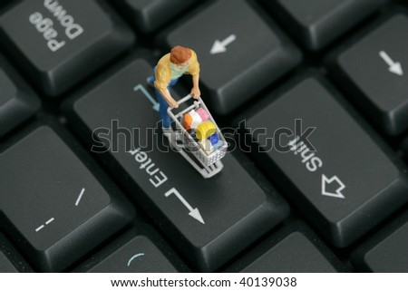 Figurine with miniature shopping cart on a computer keyboard - stock photo