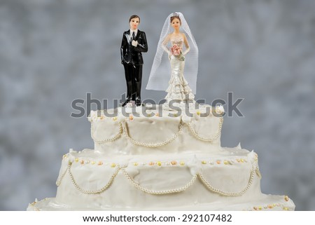 Figurines of the bride and groom on a wedding cake Corny wedding cake that symbolizes the commitment to love one another - stock photo