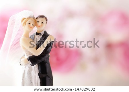 Figurines of wedding cake topper with flowers in background - stock photo