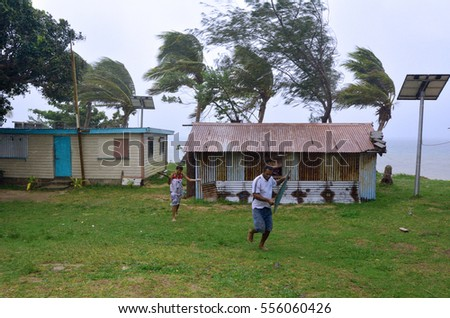 FIJI - DEC 17 2016:Fijian people run to get shelter during a Tropical Cyclone. On Feb 2016 Severe Tropical Cyclone Winston was the strongest tropical cyclone in Fiji in recorded history.