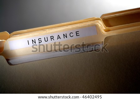 File folder for casualty and risk coverage policy papers in a stack of household documents with insurance title tab - stock photo