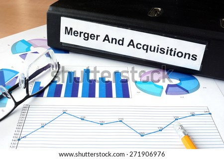 File folder with Merger and Acquisition and financial graphs. Business concept - stock photo