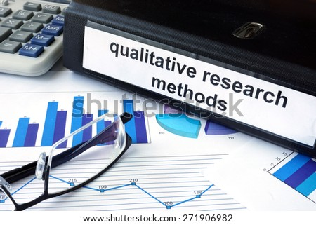 File folder with words words qualitative research methods and financial graphs. Business concept - stock photo