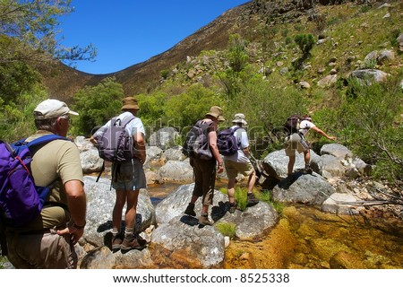 File of hikers walks across small river in awesome mountains. Shot in the Kromrivier - Du Toitskloof Nature Reserve, near Paarl, Western Cape, South Africa. - stock photo
