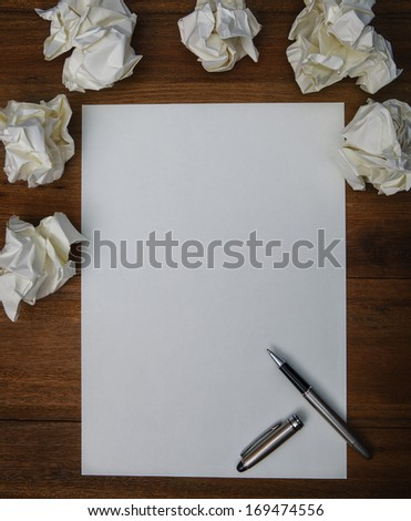 file of luxury pen ,white paper and crumpled paper on working  wood table use for idea creative of successful working hard to thinking about conceptual work flow - stock photo