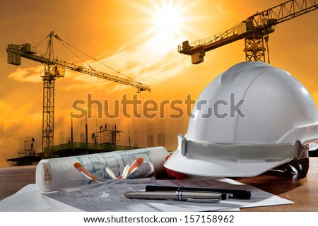 file of safety helmet and architect plant on wood table with sunset scene and building construction - stock photo