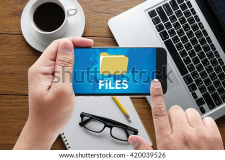 FILES message on hand holding to touch a phone, top view, table computer coffee and book - stock photo
