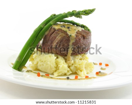 Filet mignon over mashed potatoes with asparagus on a white plate isolated on white. - stock photo