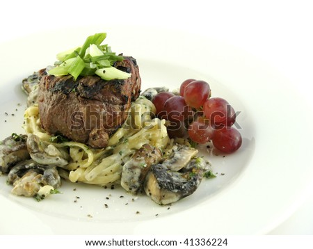 Filet mignon over pasta with grapes on a white plate isolated on white. - stock photo