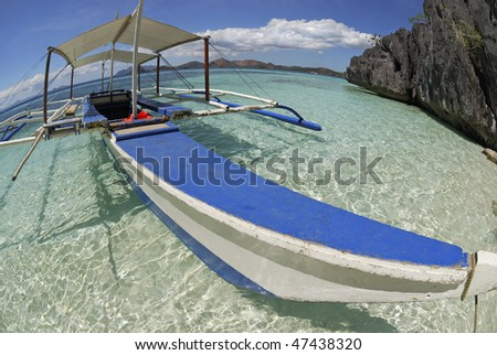 "Filipino traditional boat, idyllic ""vacations"" seascape with beautiful weather, blue sky and clear water. Fish-eye lens"
