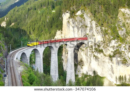 FILISUR, SWITZERLAND - JUNE 21, 2015: Landwasser Viaduct with train. Designed by Alexander Acatos, it was built between 1901 and 1902 by Müller & Zeerleder for the Rhaetian Railway. Rhaetian railway - stock photo