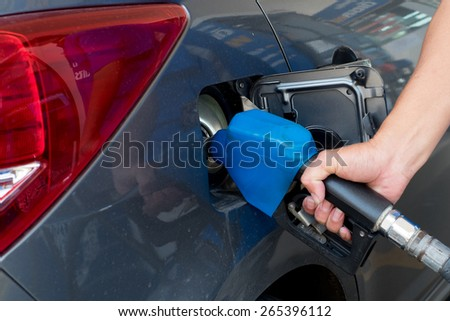 fill the petrol with hand on the nozzle - stock photo