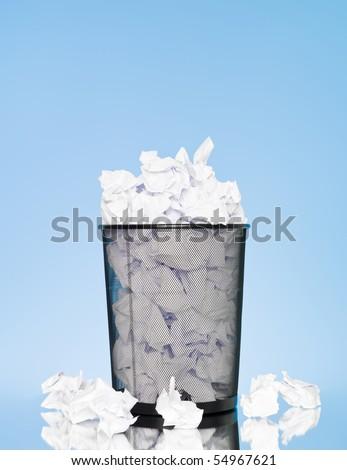 Filled wastebasket on blue background - stock photo