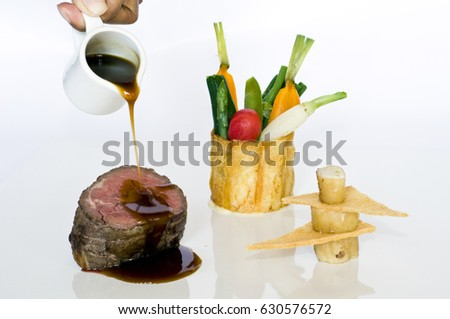 Fillet mignon with au jus, fresh vegetable medley, and crisp pastry bone marrow stack photographed on white background.
