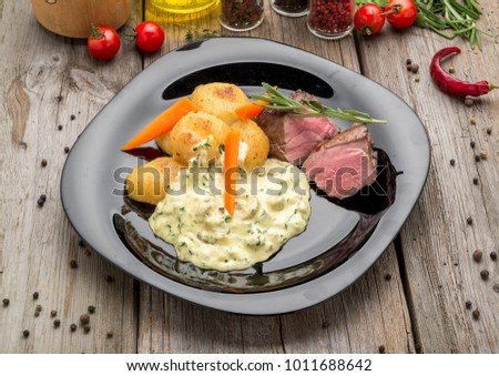 Fillet of beef with mushroom sauce and potatoes, on a wooden table