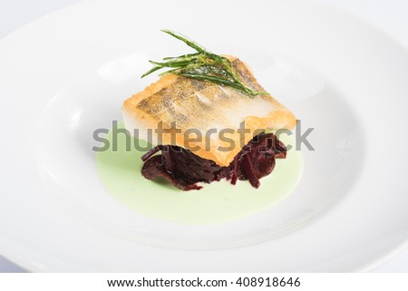 fillet of sea bass cooked with sauce and garnish on a plate