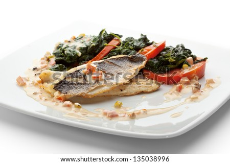Fillet of Seabass with Tomato and Mussels Sauce. Garnished with Spinach and Tomato - stock photo