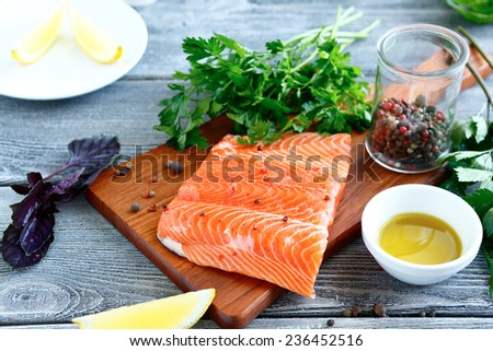 Fillet  Salmon with fresh herbs and lemon on a board. Seafood - stock photo