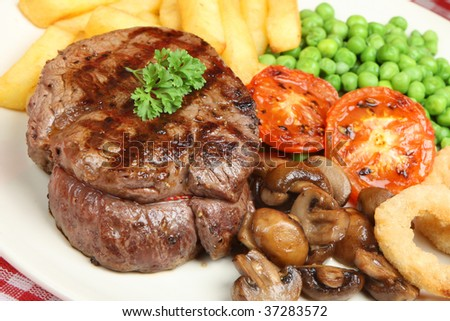 Fillet steak with chips, mushrooms, peas and onion rings - stock photo