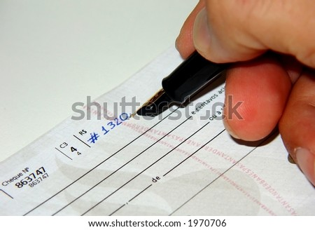 Filling a check with a pen - stock photo