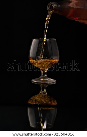 filling a glass of brandy on a black background. - stock photo