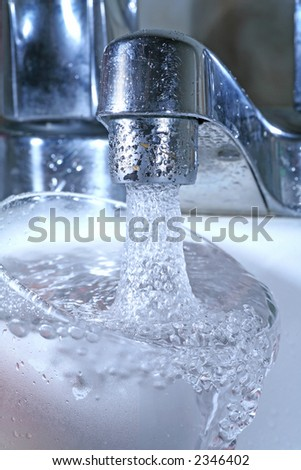 filling a glass with cool clean water from a tap. nice detail. - stock photo